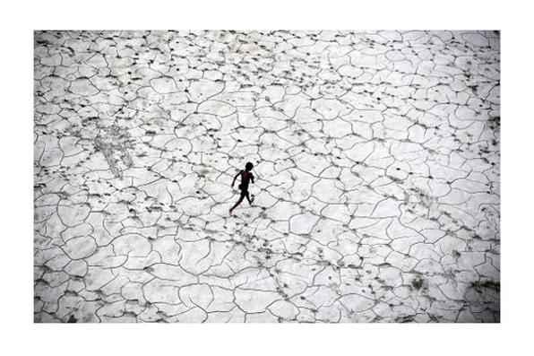 Criança brinca em rio seco na cidade indiana de Allahabad. Foto: Sanjay Kanojia/AFP Photo -