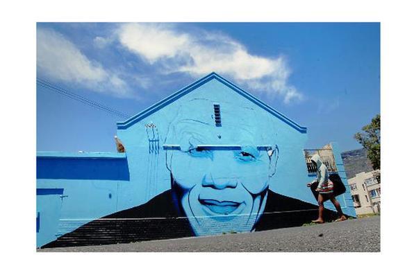 Pintura do rosto do ex-presidente sul-africano Nelson Mandela, em uma propriedade da Cidade do Cabo. Foto: Masixole Feni/AFP Photo  -