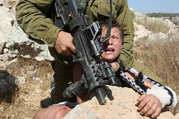 Fam�lia de palestinos entra em confronto com soldado israelense (Soldado israelense imobiliza um menino palestino, o que fez sua fam�lia reagir para libert�-lo. O confronto ocorreu ap�s um protesto em Nabi Saleh, na Cisjord�nia.Foto: AFP PHOTO / ABBAS MOMANI)