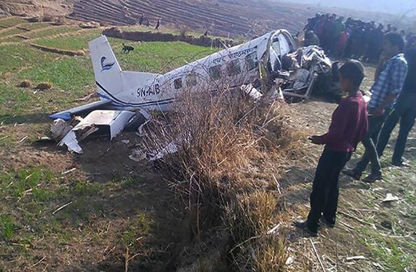 Curiosos observam os destroços do avião nepalês da companhia Kasthamandap Air que sofreu um acidente nesta sexta-feira. Os dois pilotos morreram, mas todos os nove passageiros sobreviveram ao acidente. Foto: Kamal Shahi/AFP -  Kamal Shahi/AFP