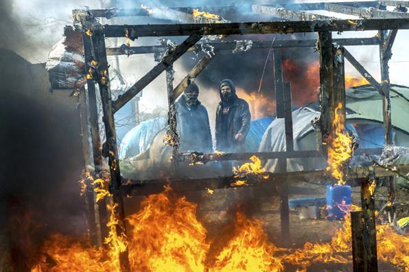 Homens assistem à destruição de barracos no campo de migrantes na cidade portuária de Calais, no norte da França.Foto: Philippe Huguen/AFP -