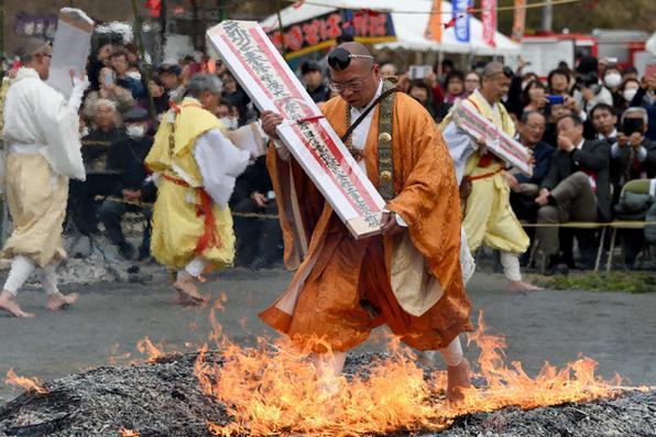 Budista anda sobre chamas  durante  cerimônia do 'Hi-watari', para celebrar a chegada da primavera, no templo Fudoki, em Nagatoro, no Japão. Foto: Toshifumi Kitamura/AFP  -