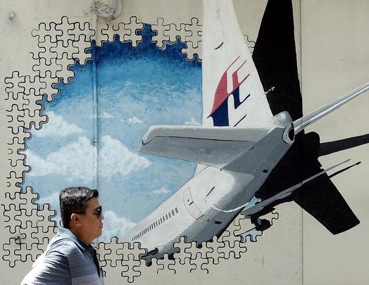 Um homem caminha em frente a um mural do avião desaparecido da Airlines MH370 em uma rua em Shah Alam na cidade de Selangor, na Malaysia, no segundo aniversário do desaparecimento do avião. Foto: Manan Vatsyayana/AFP  -