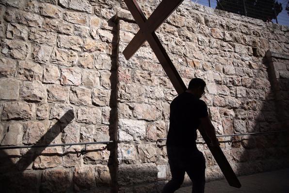 Um peregrino CatólicO carrega uma cruz de madeira ao longo da Via Dolorosa ( Caminho do Sofrimento ) na Cidade Velha de Jerusalém durante a procissão Sexta-feira Santa em 25 de março de 2016. Muitos peregrinos cristãos tomaram parte nas procissões ao longo da rota , onde segundo a tradição, Jesus Cristo carregou a cruz durante seus últimos dias. / AFP / Gali Tibbon  -  / AFP / Gali Tibbon