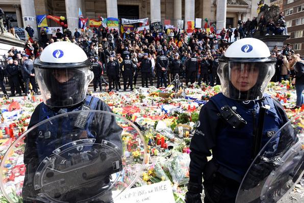 A polícia de choque protege a área na praça em Bruxelas, em 27 de março de 2016. Como a praça foi invadida por cerca de 200 hooligans de extrema-direita, a polícia disparou água num canhão. A praça se tornou um memorial às vítimas dos ataques de Bruxelas. A polícia entrou em ação depois de cerca de 200 desordeiros vestidos de preto gritando slogans nacionalistas e anti -imigrantes  na Place de la Bourse , onde as pessoas estavam se reunindo em uma demonstração de solidariedade com as vítimas .  / AFP / PATRIK STOLLARZ - / AFP / PATRIK STOLLARZ
