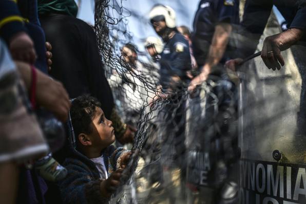 Menino observa as forças policiais de choque durante um protesto realizado por migrantes e refugiados para pedir a reabertura das fronteiras em seu acampamento improvisado na aldeia fronteira norte do Idomeni.  Foto:  Bülent Kilic/AFP  -