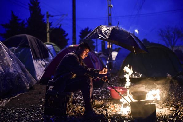 Refugiado em um acampamento improvisado na aldeia  grega do Idomeni.Foto Bulent  kilic/AFP -