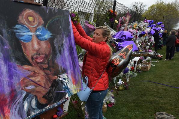 Fãs de Prince levam flores ao Memorial em sua homenagem no entorno do  Paisley Park .Foto: Mark Ralston/AFP  -