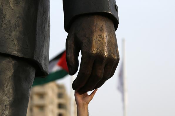 Um palestino toca a mão de uma estátua gigante de Nelson Mandela após a sua inauguração na cidade de Ramallah, Cisjordânia .  / FOTO AFP / ABBAS Momani  - / FOTO AFP / ABBAS Momani