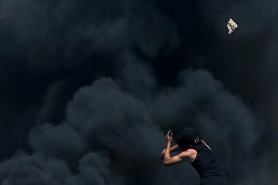 FOTOS DO DIA (Um manifestante palestino arremessa pedras na frente de pneus em chamas durante confrontos com as for�as de seguran�a de Israel na em uma manifesta��o contra a desapropria��o de terras palestinas. AFP PHOTO / JAAFAR ASHTIYEH )