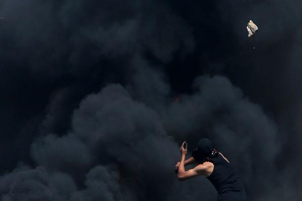 Um manifestante palestino arremessa pedras na frente de pneus em chamas durante confrontos com as forças de segurança de Israel na em uma manifestação contra a desapropriação de terras palestinas. AFP PHOTO / JAAFAR ASHTIYEH - AFP PHOTO / JAAFAR ASHTIYEH