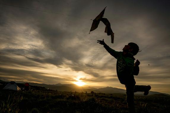 FOTOS DA SEMANA (Um menino brinca com sua pipa ao p�r do sol em um acampamento improvisado para os migrantes e refugiados na fronteira greco-maced�nio perto da aldeia de Idomeni./ AFP PHOTO / JOE KLAMAR )
