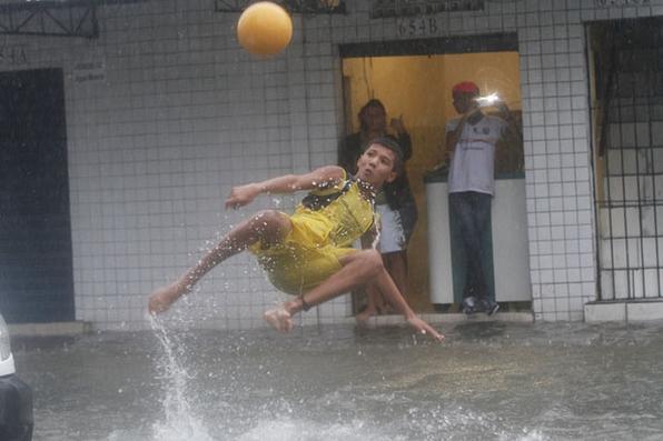 Crianças aproveitam o alagamento da Avenida norte e brincam de bola. Foto: Rafael Martins/Es. DP - Rafael Martins/Es. DP