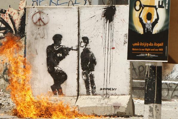 Chamas queimam grafite nos confrontos entre as forças de segurança israelenses e manifestantes palestinos durante um comício na cidade do banco ocidental de Bethlehem. AFP PHOTO / HAZEM BADER -  AFP PHOTO / HAZEM BADER