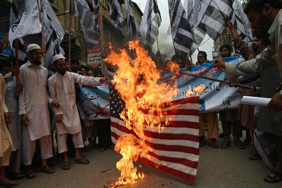 FOTOS DO DIA (Apoiantes do Paquist�o da organiza��o fundamentalista proibida Jamaat -ud- Dawa queimam uma bandeira dos EUA em um protesto em Peshawar, contra a greve tripulados dos EUA em solo paquistan�s, que matou o l�der do Taliban, mul� Akhtar Mansour .AFP PHOTO / A MAJEED )
