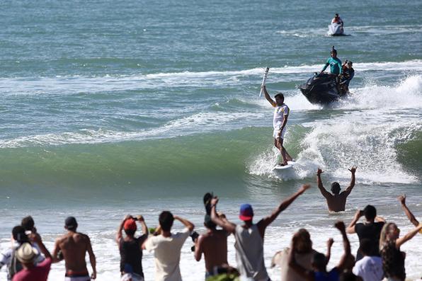Surfista Carlos Burle conduziu a tocha olímpica pelas águas da praia de Maracaípe, litoral sul de Pernambuco. Foto:  Ivo Lima/ ME. -