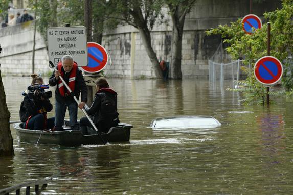 FOTOS DO DIA (Jornalistas sobre um pequeno barco passam perto de um carro imerso em rua inundada ao longo do quai Louis Bleriot no 16� arrondissement em Paris. Foto:  AFP PHOTO / BERTRAND GUAY / AFP PHOTO / BERTRAND GUAY.)