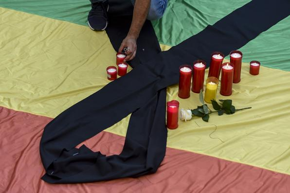 FRANÇA - Velas são colocadas na bandeira do arco-íris coberto com um pano preto em forma de luto durante uma vigília na Praça Sant Jaum,  em memória das vítimas assassinadas numa boate gay em Orlando , Florida , no pior tiroteio em massa na história dos EUA . AFP PHOTO / JOSEP LAGO - AFP PHOTO / JOSEP LAGO