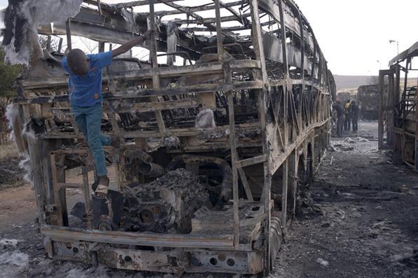 Criança de Mamelodi em ônibus que foi queimado durante os 3 dias de duração protesto em Mamelodi. Foto: AFP PHOTO / Mujahid SAFODIEN -
