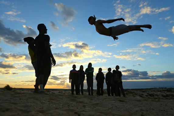 FOTOS DO DIA  (Jovens palestinos mostram suas habilidades na praia de Rafah, no sul da Faixa de Gaza. Foto: AFP PHOTO / MOHAMMED ABED.)
