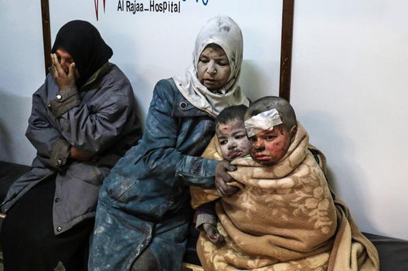 Uma mulher síria é fotografada com crianças feridas em um hospital após um ataque  no subúrbio de Damasco. AFP PHOTO / Saria ABU ZAID -