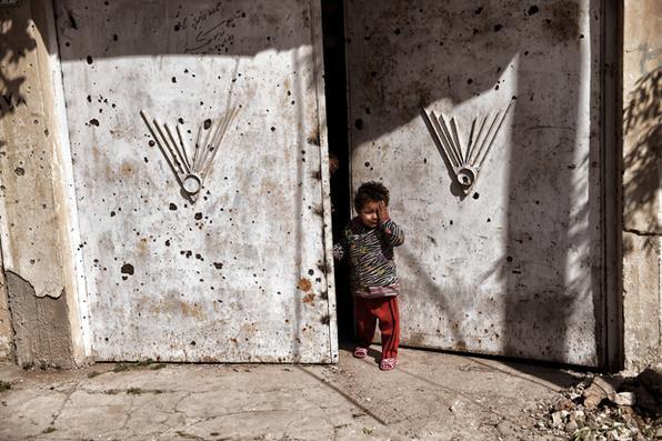 No oeste de Mosul, uma criança observa   forças iraquianas  contra os combatentes do grupo islâmico (IS) que avançam na cidade.  Forças iraquianas disseram que haviam tomado os principais escritórios do governo em Mosul. Segundo eles , fizeram um grande progresso  em sua batalha para retomar o oeste da cidade de jihadistas.Foto: ARIS MESSINIS / AFP -