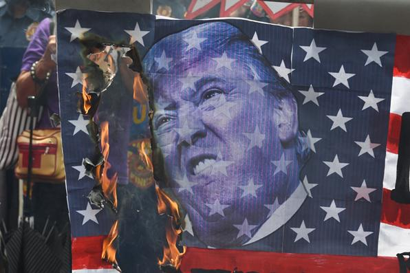 Manifestantes queimam uma bandeira americana com o retrato do presidente americano, Donald Trump, durante protesto na embaixada dos Estados Unidos, em Manila, nas Filipinas, para marcar o Dia Internacional da Mulher. Foto: AFP PHOTO / TED ALJIBE -