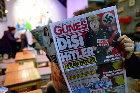 Um homem lê uma edição do jornal Gunes, um diário turco pró-governo, com a chanceler alemã Angela Merkel retratada com um uniforme nazista, um bigode como o de Hitler e fazendo a saudação Nazi em Istambul, Turquia Foto: AFP PHOTO / YASIN AKGUL -