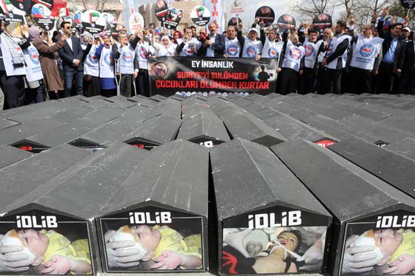 As pessoas estão na frente de caixões simbólicos com fotos de vítimas sírias e inscrições como ''Asad assassino'' e ''Putin assassino'' durante um protesto contra a Rússia por seu papel alegado em um ataque químico na província síria de Idlib,  em frente da embaixada russa, em Ancara. AFP PHOTO / ADEM ALTAN - AFP PHOTO / ADEM ALTAN