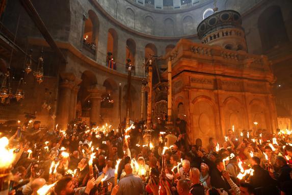 """FOTOS DO DIA (Fiéis ortodoxos cristãos mantêm velas durante a cerimônia do """"Fogo Sagrado"""" enquanto milhares se reúnem na Igreja do Santo Sepulcro na Cidade Velha de Jerusalém. Foto: GALI TIBBON / AFP.)"""