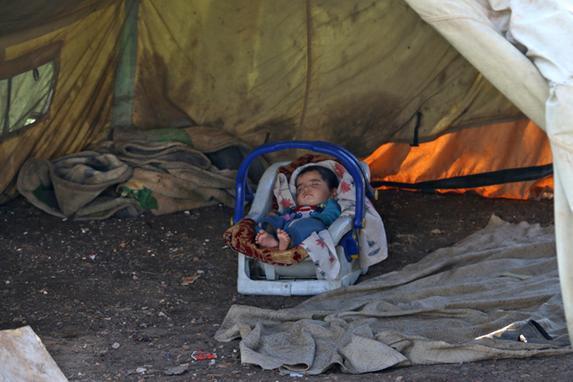 FOTOS DO DIA (Uma criança encontra-se dormindo em um carrinho de bebê numa barraca na cidade de Azaz, na beira do norte de Syria com Turquia.  AFP PHOTO / Zein Al RIFAI)