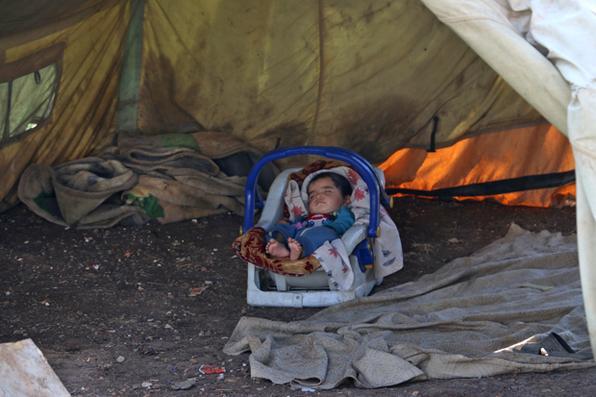 Uma criança encontra-se dormindo em um carrinho de bebê numa barraca na cidade de Azaz, na beira do norte de Syria com Turquia.  AFP PHOTO / Zein Al RIFAI - AFP PHOTO / Zein Al RIFAI