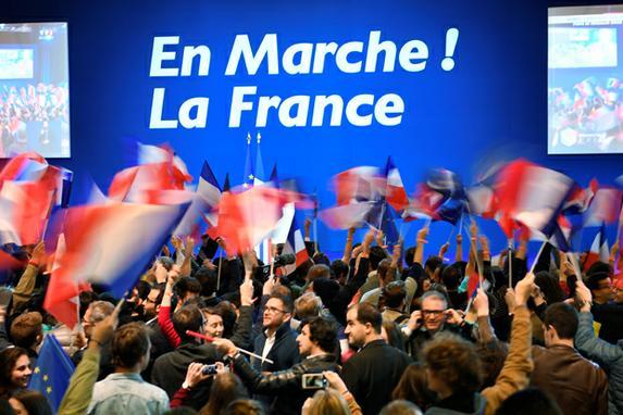 FOTOS DO DIA (Pessoas agitam bandeiras nacionais francesas antes de uma reunião do candidato presidencial francês para o En Marche! Movimento no Parc des Expositions em Paris, durante a primeira rodada da eleição presidencial. / FOTOGRAFIA AFP / Eric FEFERBERG)