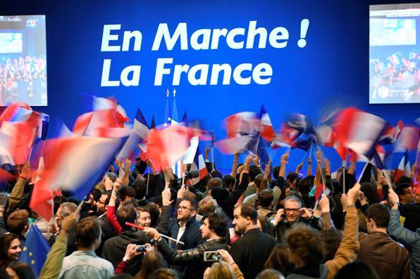 Pessoas agitam bandeiras nacionais francesas antes de uma reunião do candidato presidencial francês para o En Marche! Movimento no Parc des Expositions em Paris, durante a primeira rodada da eleição presidencial. / FOTOGRAFIA AFP / Eric FEFERBERG -  FOTOGRAFIA AFP / Eric FEFERBERG