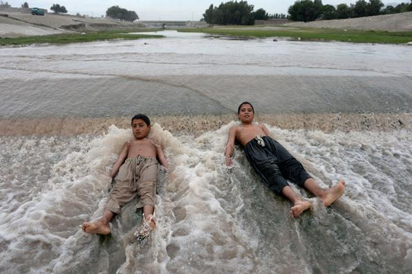 Crianças afegãs brincam na água que flui de um rio nos arredores de Jalalabad. Foto: AFP PHOTO / NOORULLAH SHIRZADA -