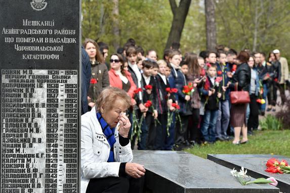FOTOS DO DIA (Mulher chora ao lado de uma lápide, gravada com os nomes das vítimas da catástrofe de Chernobyl em 1986, durante  memorial para as vítimas , em Kiev, no 31º aniversário do desastre. Foto:  AFP PHOTO / Sergei SUPINSKY)