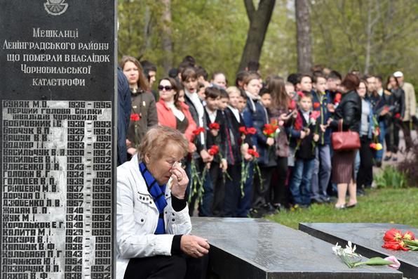 Mulher chora ao lado de uma lápide, gravada com os nomes das vítimas da catástrofe de Chernobyl em 1986, durante  memorial para as vítimas , em Kiev, no 31º aniversário do desastre. Foto:  AFP PHOTO / Sergei SUPINSKY -