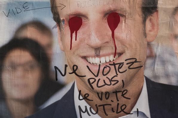 Um poster eleitoral do candidato a eleição presidencial francesa Emmanuel Macron  é coberto com graffitis em Paris. Foto:  AFP PHOTO / JOEL SAGET -