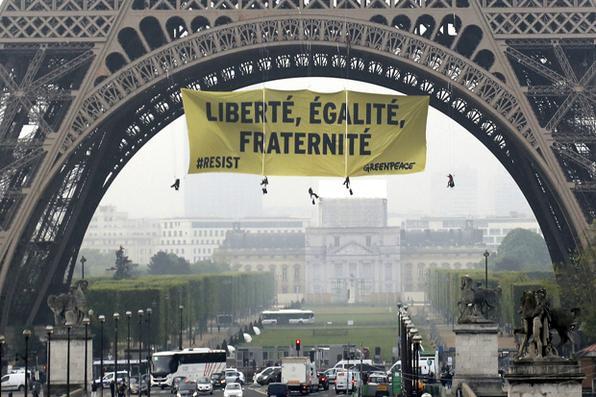 Uma foto mostra uma bandeira que diz ''liberdade, igualdade e fraternidade'', pendurada  pelos ativistas do Greenpeace na Torre Eiffel, em Paris, para protestar contra o partido de extrema-direita Frente Nacional (FN), dois dias antes do segundo turno da eleição presidencial. Foto:  AFP PHOTO / Jacques DEMARTHON / ALTERNATIVE CROP -