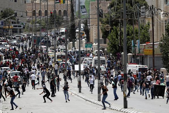 Manifestantes palestinos lançam pedras contra as forças de segurança israelenses durante os confrontos,  para marcar o 69º aniversário da ''Nakba'' na cidade de Belém, na Cisjordânia. Foto:  AFP PHOTO / THOMAS COEX -