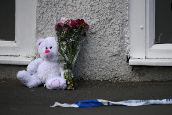 FOTOS DO DIA (Tributo floral e um urso de pelúcia são retratados ao lado da fita da polícia perto da arena de Manchester, em Manchester, noroeste Inglaterra, após um ataque terrorista mortal no concerto de Ariana Grande na arena de Manchester a noite antes. Foto: AFP PHOTO / Oli SCARFF.)