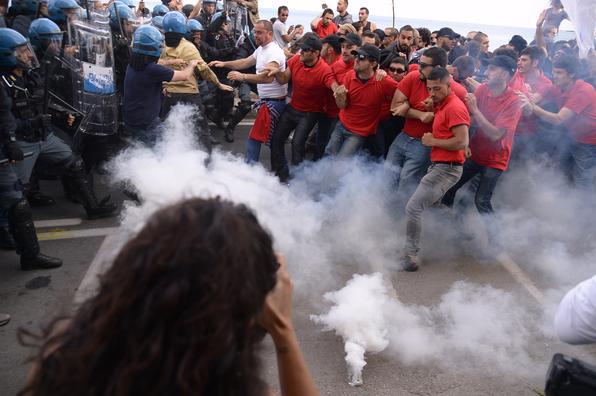 Manifestantes enfrentam policiais durante uma manifestação contra a Cúpula do G7 em Giardini-Naxos, perto do local da cúpula dos Chefes de Estado e de Governo do G7 em Taormina, na Sicília. Foto: AFP FOTO / Filippo MONTEFORTE. -