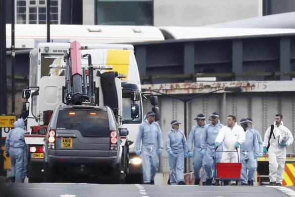 Uma furgão branco usado no ataque da ponte de Londresé visto em cima de um caminhão, enquanto oficiais de polícia forense trabalham na London Bridge, como parte de suas investigações após o ataque terrorista na ponte e No próximo Mercado de Borough.  Sete pessoas foram mortas por três assaltantes na London Bridge e no movimentado distrito da vida noturna de Borough Market, disse o chefe da força policial de Londres no domingo. / AFP PHOTO / Odds ANDERSEN - AFP PHOTO / Odds ANDERSEN