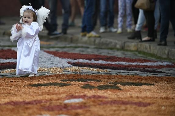 FOTOS DO DIA (Menina durante a celebração católica do Corpus Christi em uma rua de Ouro Preto, a cerca de 100 km de Belo Horizonte, Brasil. Foto:  AFP PHOTO / DOUGLAS MAGNO.)