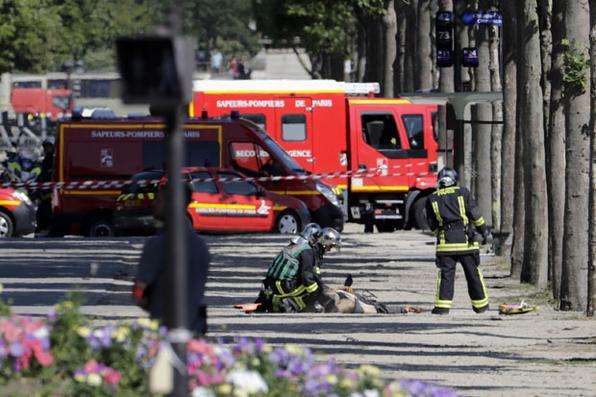 Socorristas olham corpo de um suspeito deitado em uma área fechada da avenida Champs-Elysees em Paris, depois que um carro bateu numa van da polícia antes de incendiar. AFP PHOTO / Thomas SAMSON - AFP PHOTO / Thomas SAMSON