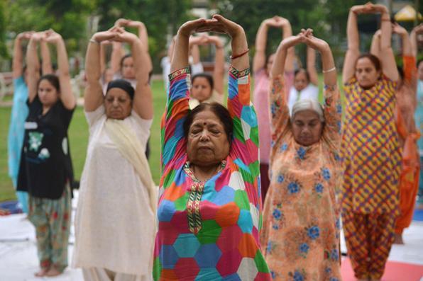Praticantes indianos de ioga participam de uma sessão em um parque em Amritsar,  um dia antes do Dia Internacional do Yoga. Foto:  AFP PHOTO / NARINDER NANU -