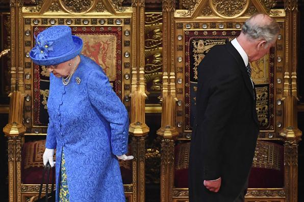 Rainha Elizabeth II da Grã-Bretanha e seu filho, o Príncipe Carlos de Grã-Bretanha, Príncipe de Gales, preparam-se para ocupar seus lugares quando chegam na Câmara dos Lordes durante a Abertura do Parlamento no Parlamento das Casas do Parlamento em Londres. Foto: AFP PHOTO / POOL / Carl Court -