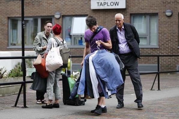 Um homem leva suas roupas do apartamento residencial da Taplow Tower no Chalcots Estate, no norte de Londres, quando os residentes evacuam a área devido a preocupações com segurança contra incêndios.  - AFP PHOTO / Tolga AKMEN