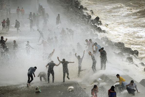 As pessoas se reúnem pela marinha Drive a beira do mar para quebrar as ondas na maré alta em Mumbai. Foto: AFP PHOTO / PUNIT PARANJPE. -