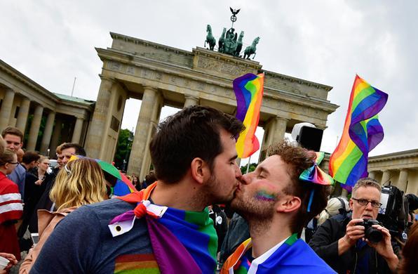 Dois homens se beijam enquanto participam de uma manifestação de homossexuais e lésbicas em frente ao Portão de Brandenburgo, em Berlim. O parlamento alemão legalizou o casamento do mesmo sexo, dias após a chanceler Angela Merkel ter dito que permitiria que seus legisladores conservadores seguissem sua consciência na votação. / AFP PHOTO / Tobias SCHWARZ -  AFP PHOTO / Tobias SCHWARZ